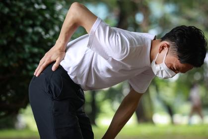 腰に痛みを感じる男性