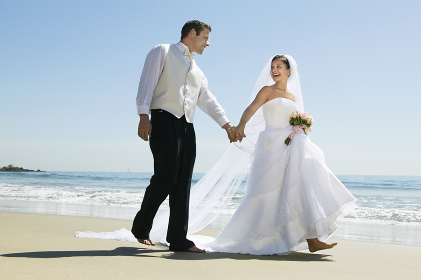Newlywed Couple Holding Hands While Walking On Beach