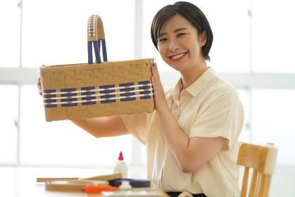 クラフトバンドで作ったカゴを持つ女性