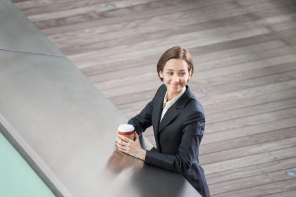 テイクアウトコーヒーを手に持つ女性