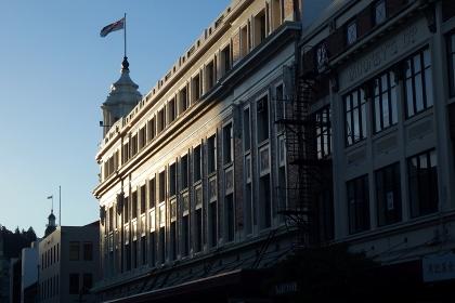 外壁の一部が朝日に輝く、重厚な石造りの西洋建築