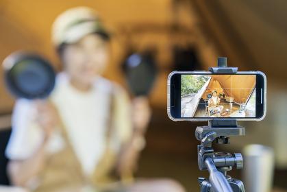 キャンプをして、テントの中でスマートフォンで撮影する若い女性
