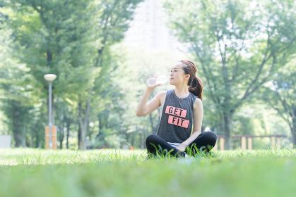 公園で運動(ヨガ)中に水分を補給する女性
