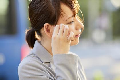 髪を耳にかける日本人ビジネスーウーマン