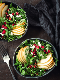 Vegan salad bowl with arugula, pear, pomegranate, cheese