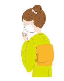 手を合わせ祈るマスクと着物姿の女性