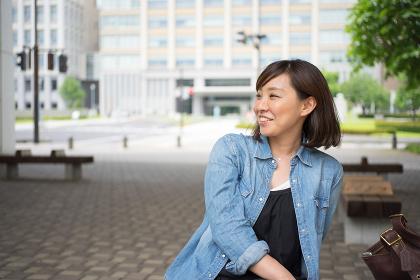 屋外のベンチに座る女性