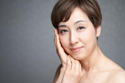 両手を頬に当てる中年の日本人女性