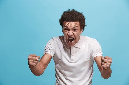 The young emotional angry man screaming on blue studio background