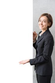 スーツ姿で案内する若い女性(コピースペース)
