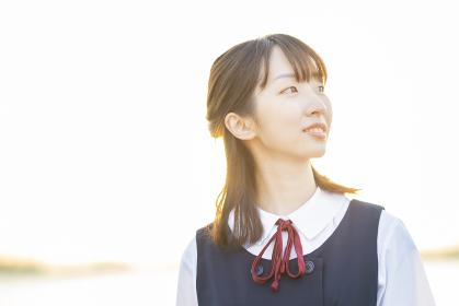 夕陽に包まれるアジア人女性の高校生
