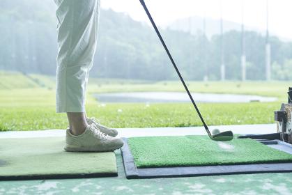 ゴルフ場で練習をする女性の足元