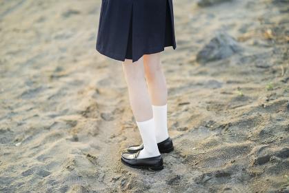 渚を歩くアジア人女性の高生