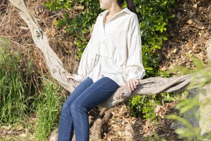 木の幹でできたブランコに腰掛ける女性