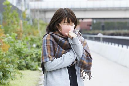 咳をするカラーマスクをつけた日本人女性