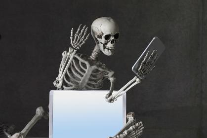 スマホを見て驚く骸骨
