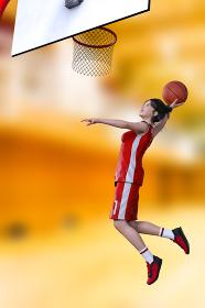 バスケットボールをする元気な女の子が赤ユニフォームを着てゴールにダンクシュートをする
