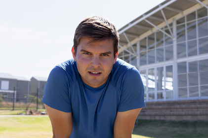 Portrait close up of a Caucasian male runner training at a sports field, wearing a blue t shirt, looking to camera and leaning forward recovering after a run