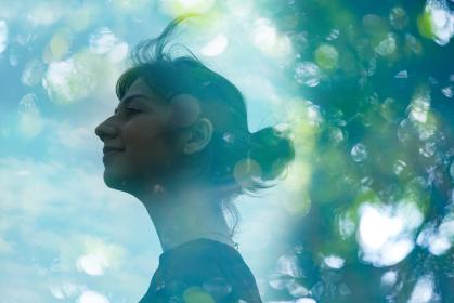 エコロジーイメージ・女性の横顔とアウトフォーカスで撮影した森の合成CG