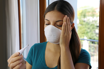 COVID-19 Pandemic Coronavirus Mask Fever Woman Checking Temperature with Thermometer at Home Symptom of SARS-CoV-2. Girl with mask on face check fever one of the symptoms of Coronavirus Disease 2019.