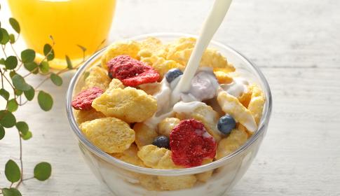 ミルクを注いでいる朝食のシリアルやフレーク