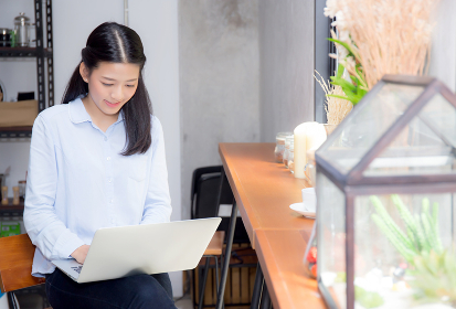 Beautiful asian young woman working online on laptop sitting at