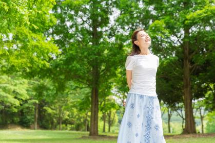 新緑でリラックスする笑顔の女性 全身