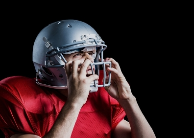 Aggressive american football player holding his helmet