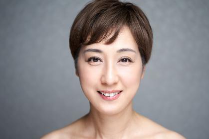 カメラ目線でほほ笑む中年の日本人女性