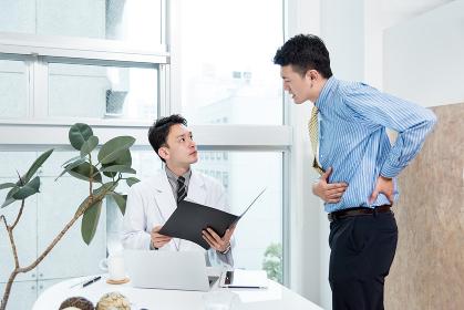 腹痛を訴える男性と診察をする医者