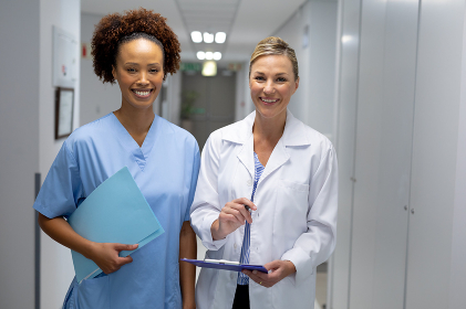 Portrait of two diverse female doctors standing in hospital corridor smiling to camera. medicine, health and healthcare services.