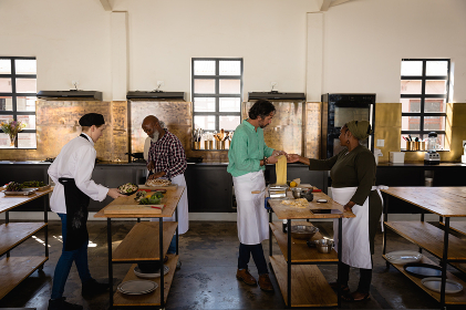 Side view of a multi-ethnic Senior group of adults at a cookery class, standing at wooden tables and preparing food, assisted by a Caucasian female chef wearing chefs whites and a black hat and apron