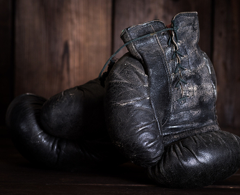pair of very old shabby black leather boxing gloves