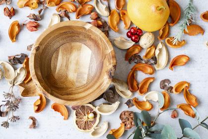 大理石のテーブルの上にセットされた木製のお皿と植物で作られた装飾物