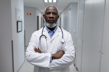 Portrait of senior male doctor with stethoscope wearing lab coat, arms crossed in hospital corridor. medical professional at work.