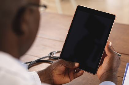 Mid section of african american senior male doctor holding digital tablet with copy space at home. distant communication and telemedicine consultation concept.