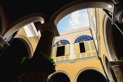 アーチ型の建物の中庭から見上げる青空