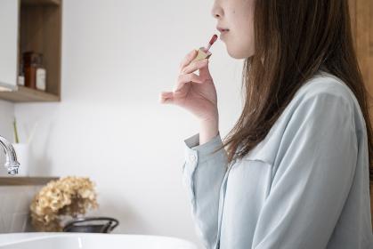 洗面化粧室でメイクをする若い女性