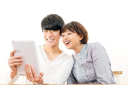 タブレットPCを見る若いカップル