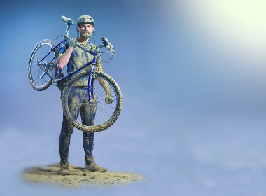 The man with bike in sand standing on abstract background. Collage