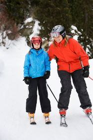 Mother and daughter skiing together