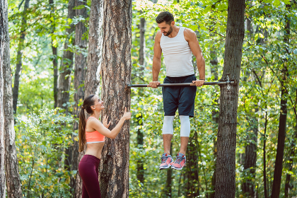 Woman watches man doing exercises on high bars