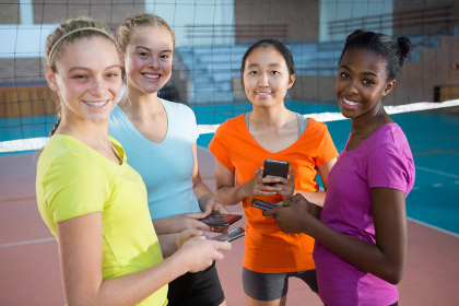 Smiling female players using mobile phones in volleyball court