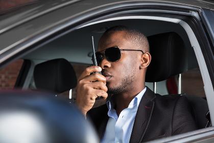 Man Sitting Inside Car Talking On Walkie Talkie