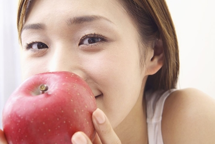 林檎にキスする女性