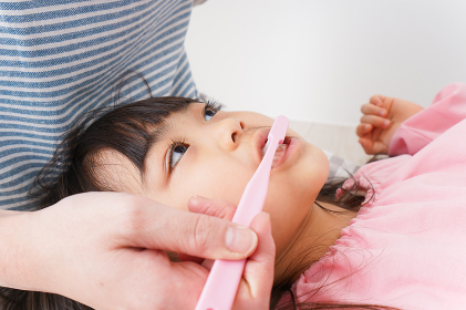 子供の歯を磨くお母さん