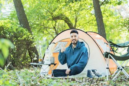 テントの前で笑顔でポーズする男性