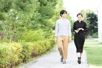 新緑が爽やかな歩道を歩く男女