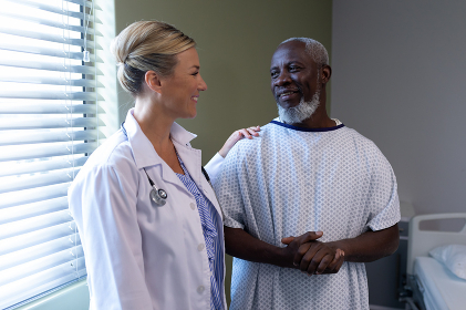 Diverse female doctor and male patient in hospital room smiling to each other. medicine, health and healthcare services.