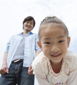 笑顔で覗き込む女の子と父親